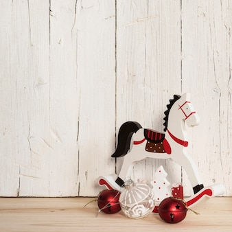 Samenstelling van kerstversieringen en houten paard met kopie ruimte