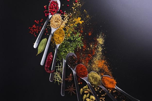 Samenstelling van kleine lepels vol kruiden en specerijen om te koken op een zwarte achtergrond