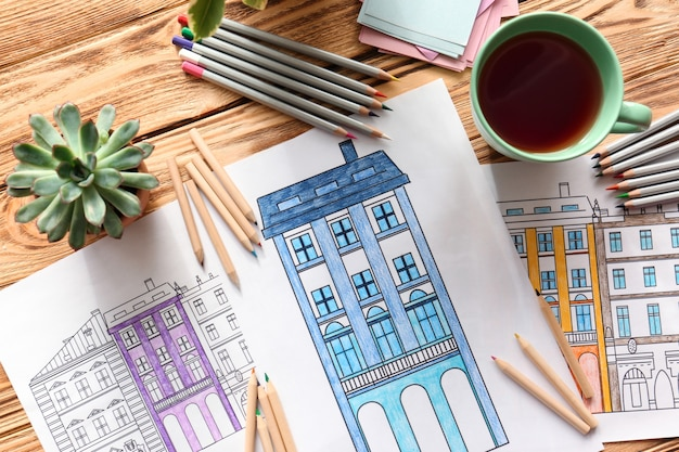 Samenstelling van kleurplaten en potloden op houten tafel