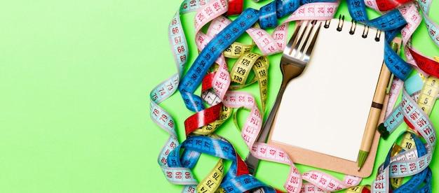 Samenstelling van kleurrijke meetlinten, vork, pen en blocnote op groene achtergrond. bovenaanzicht van dieetcontrole en lege ruimte voor uw ontwerp