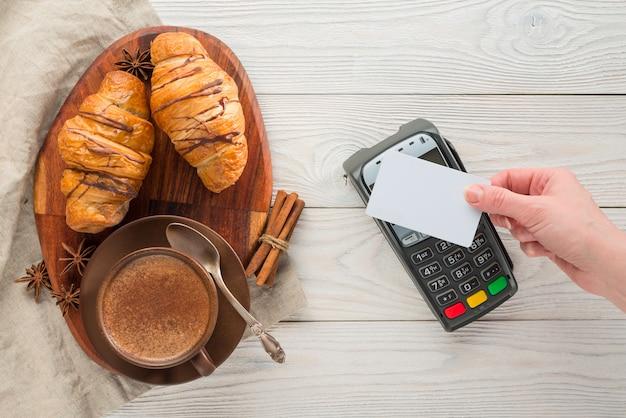 Samenstelling van koffie en croissants met bankbetalingsterminal op een houten achtergrond
