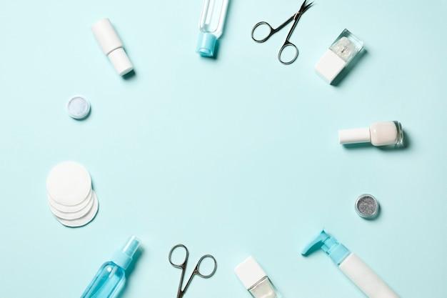 Samenstelling van manicure tools en cosmetica en nagellakken op een blauwe achtergrond. plaats voor tekst.