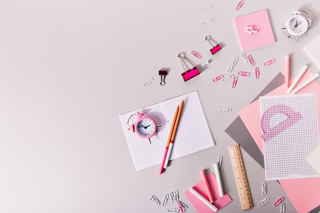 Samenstelling van meisjesachtig kantoorbenodigdheden in roze en witte tinten.