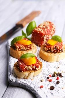 Samenstelling van mes, smakelijke sandwiches met salamiworst, basilicumblad op snijplank op houten tafel