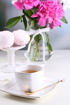 Samenstelling van mooie pioenrozen in vaas, thee in beker en marshmallow op tafel