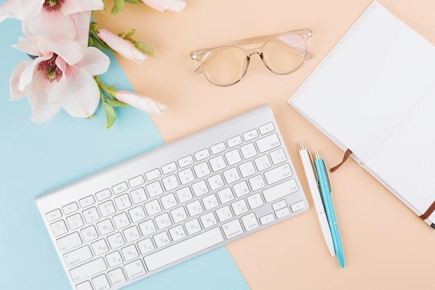 Samenstelling van notitieboekje, toetsenbord, oogglazen, bloemen en pennen