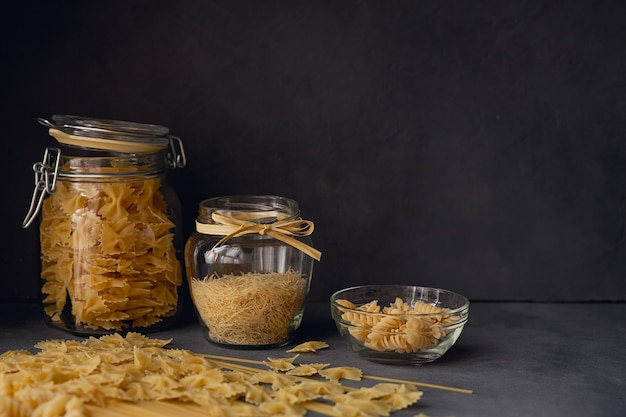 Samenstelling van ongekookte italiaanse pasta. spaghetti, farfalle, fusilli op donkere houten achtergrond. rauwe pasta achtergrond.