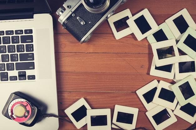Samenstelling van oude fotocamera, laptop en dia's