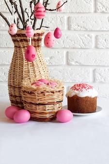 Samenstelling van pasen met versierde boomtakken in een rieten vaas, roze gekleurde eieren in rieten mand en pasen-cake op witte achtergrond. kopieer ruimte