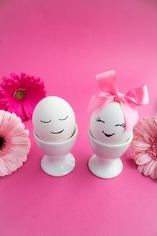 Samenstelling van pasen met witte eieren in witte onderzetters op een roze tafel. kopieer ruimte.