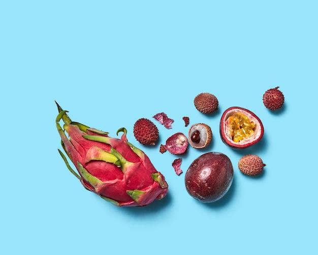 Samenstelling van passievrucht, lychee, pitahaya en fruitschil op een blauwe achtergrond met kopieerruimte. tropisch gezond fruit. plat leggen