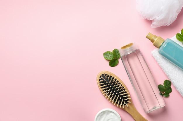 Samenstelling van persoonlijke hygiëne met flessen cosmetica op roze achtergrond