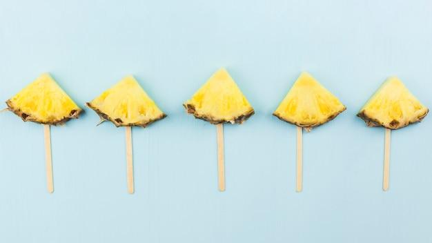 Samenstelling van plakjes ananas op toverstokken
