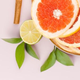 Samenstelling van plakjes grapefruit met limoen en groene bladeren in de buurt van kaneel