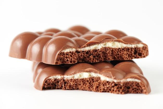 Samenstelling van repen en stukjes poreuze melkchocolade met een kokosnoot laag close-up op een witte achtergrond geïsoleerd