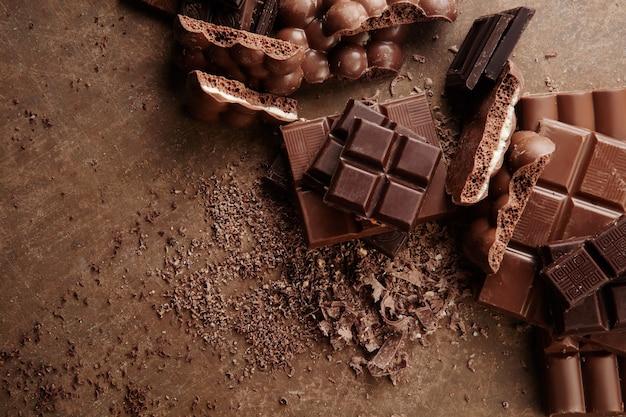 Samenstelling van repen en stukjes van verschillende melk en donkere chocolade, geraspte cacao op een bruine achtergrond bovenaanzicht close-up