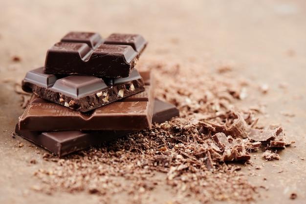 Samenstelling van repen en stukjes van verschillende melk en donkere chocolade, geraspte cacao op een bruine achtergrond zijaanzicht close-up