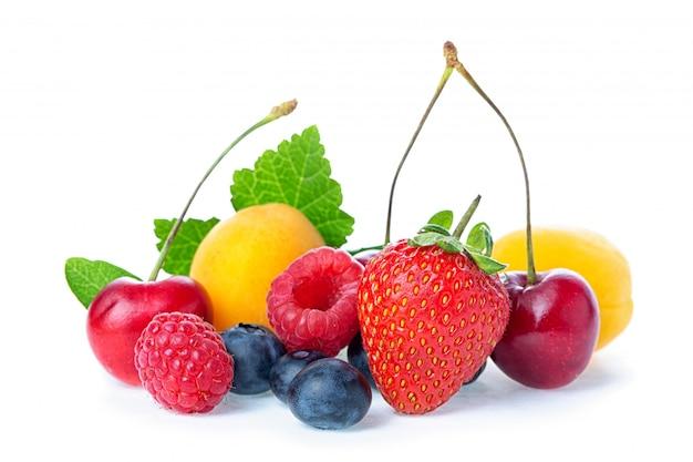 Samenstelling van rijpe rode zoete kers met hoorns, frambozen, abrikozen, aardbeien en bosbessen met blad geïsoleerd op witte achtergrond