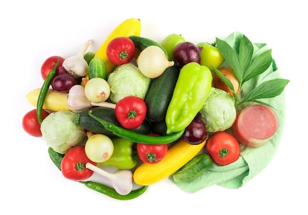 Samenstelling van rijpe verse groenten, een glas groentesap en een groene tak met waterdruppels.