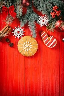 Samenstelling van smakelijke peperkoekkoekjes en kerstdecor op rode houten achtergrond