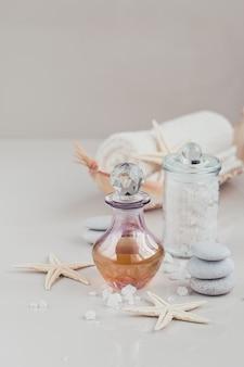 Samenstelling van spa-behandeling met parfum of aromatische oliefles omgeven door bloemen, op een helder oppervlak