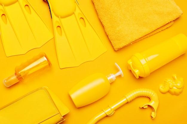 Samenstelling van strandkleding en accessoires op een geel