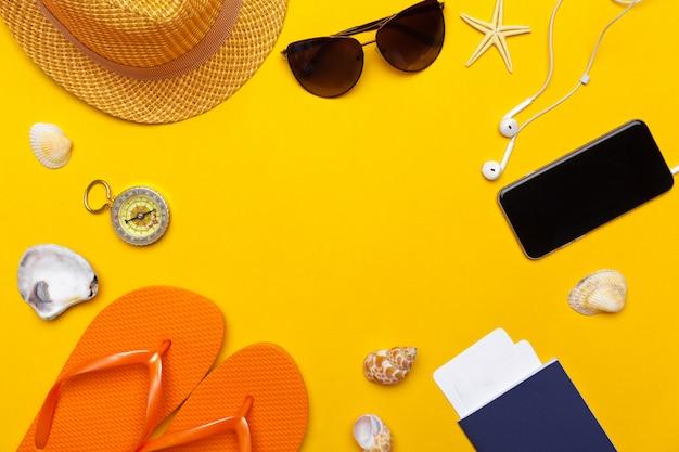 Samenstelling van strandkleding en accessoires op een gele achtergrond