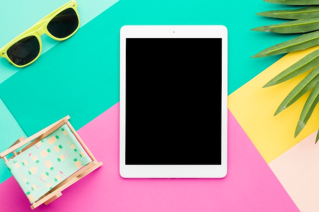 Samenstelling van strandontspanning met tablet op multicolored oppervlakte