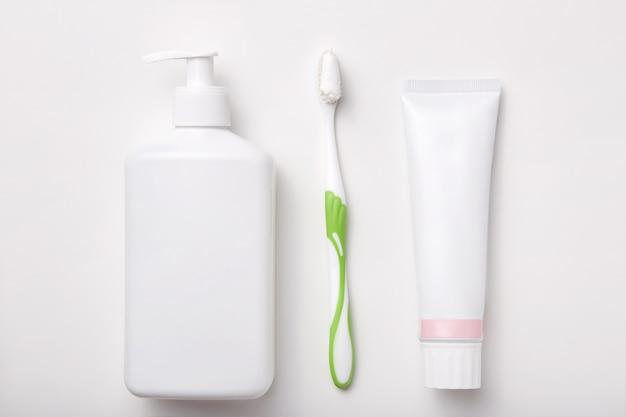 Samenstelling van tandenborstel, tandpasta en fles zeep of gel op wit wordt geïsoleerd. cosmetische producten. plat liggen