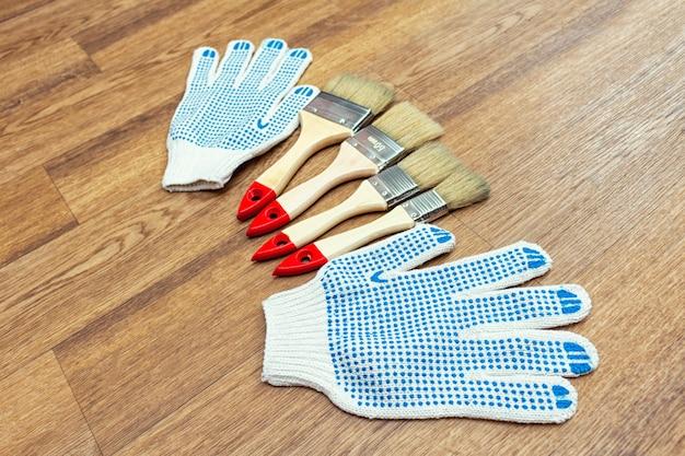 Samenstelling van tekengereedschappen met penselen, handschoenen en verfroller op de houten vloer