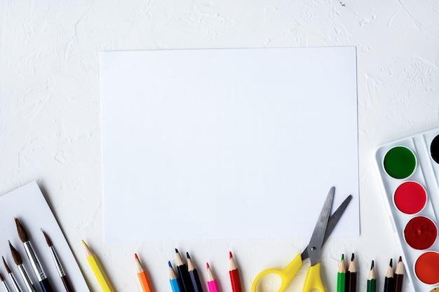 Samenstelling van verfapparatuur. potloden, stiften, penselen, verf en papier. lichte achtergrond