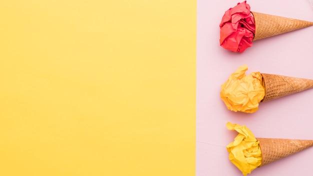 Samenstelling van verfrommeld kleurrijke papier en ijshoorntjes
