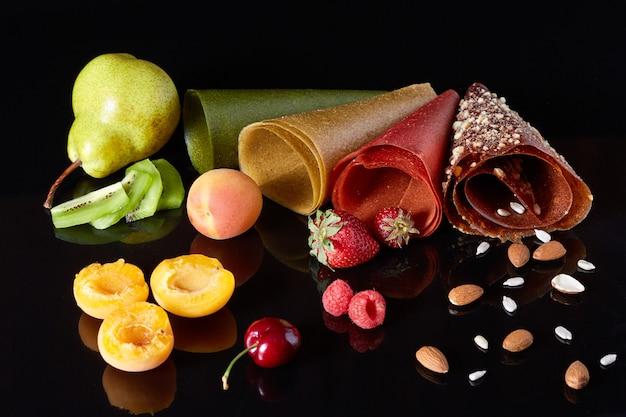 Samenstelling van vers fruit en een rol fruit leer op een zwarte achtergrond