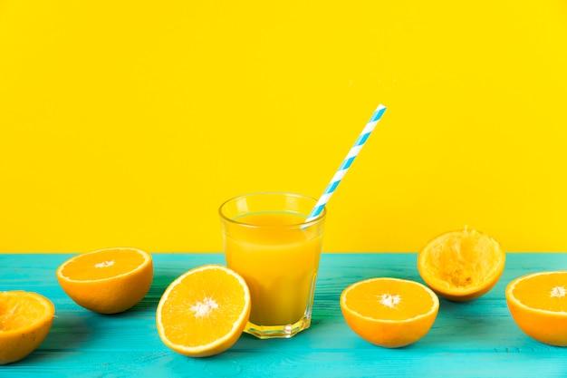 Samenstelling van vers jus d'orange met gele achtergrond