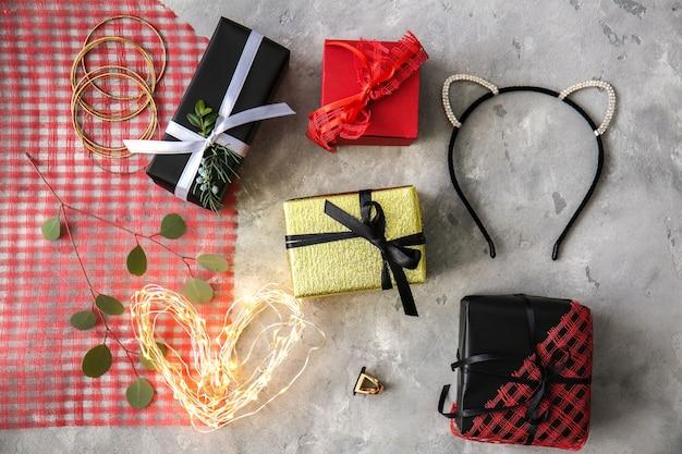 Samenstelling van versierde geschenkdozen en accessoires op grijze tafel