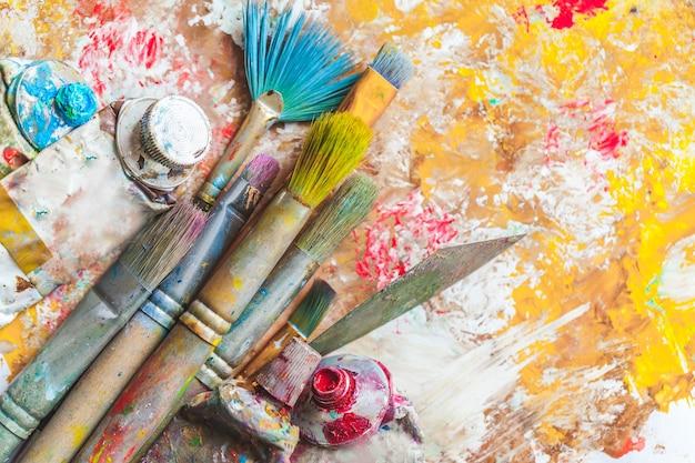 Samenstelling van vuile schilderborstels op kleurrijke achtergrond