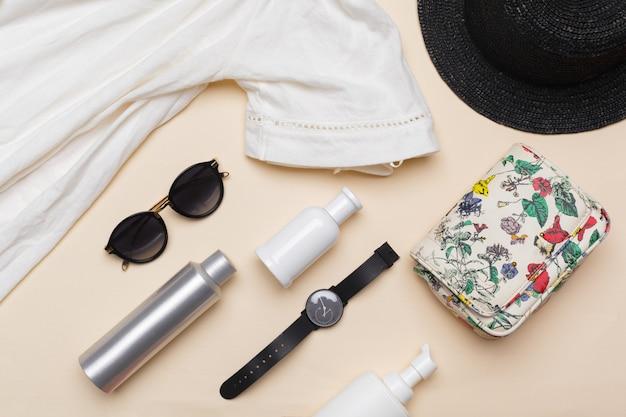 Samenstelling van witte jurk, zwarte strohoed, zonnebril, handtas en andere accessoires op pastel bovenaanzicht
