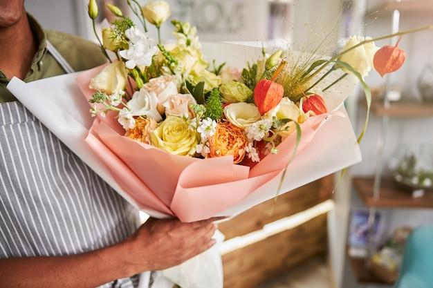 Samenstelling van witte, rode, oranje en gele bloemen die samen in een verpakkingspapier liggen in de hand van de bloemist