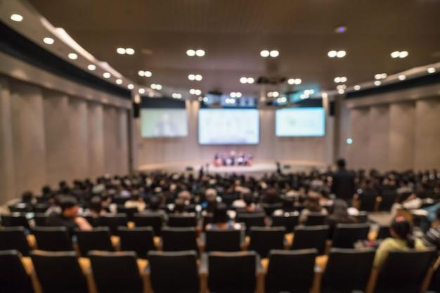 Samenvatting vage foto van conferentiezaal of seminarieruimte met sprekers op het stadium