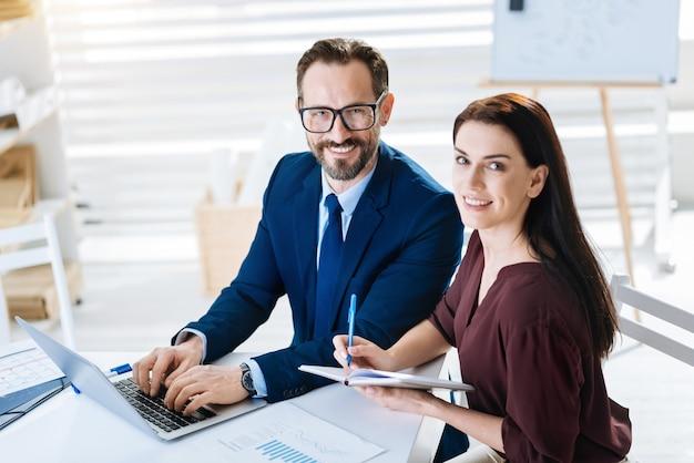Samenwerken. bovenaanzicht van vrolijke vrolijke twee collega's staren naar de camera terwijl man met laptop en vrouw opschrijven