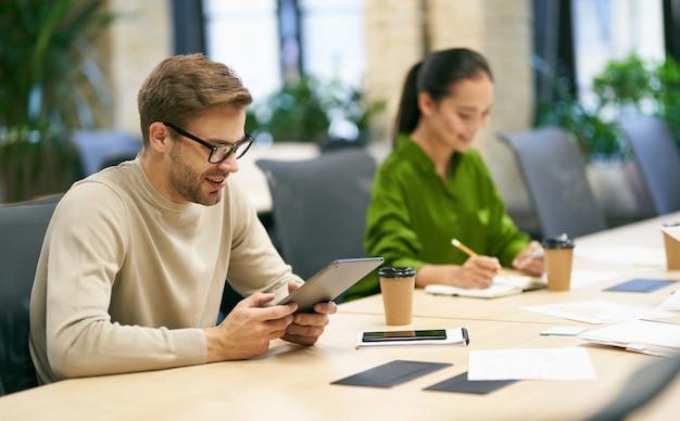 Samenwerkend jonge lachende blanke man met bril met behulp van digitale tablet zittend