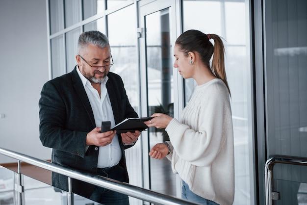 Samenwerking geeft goede resultaten. meisje dat documenten toont aan haar baas in brillen en grijze baard