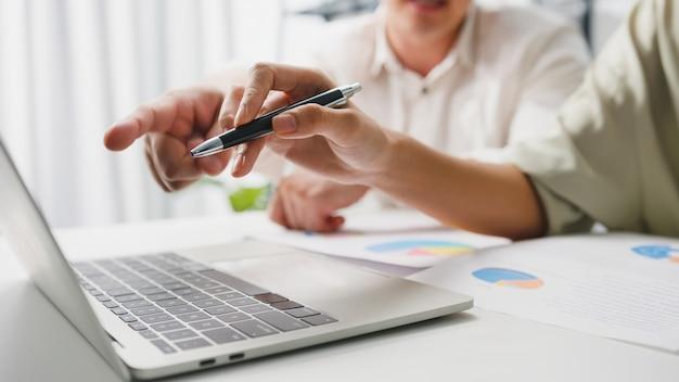 Samenwerkingsproces van multiculturele zakenmensen met behulp van laptoppresentatie en communicatievergaderingen voor brainstormideeën