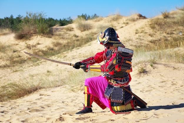 Samoerai met zwaard op het zand. mannen in samoeraienpantser op het zand. origineel personage