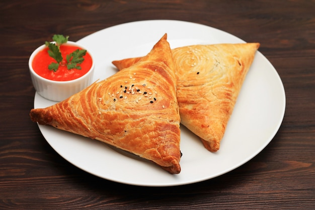 Samosa een pittige mix van vlees gewikkeld in een gefrituurd driehoekig gebakspakket in een bord op een donkere ondergrond.