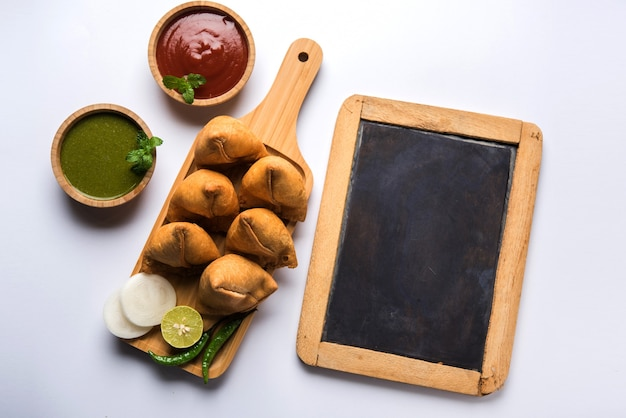 Samosa snack geserveerd met schoolbord of leisteen voor tekst, geserveerd met ketchup en muntchutney