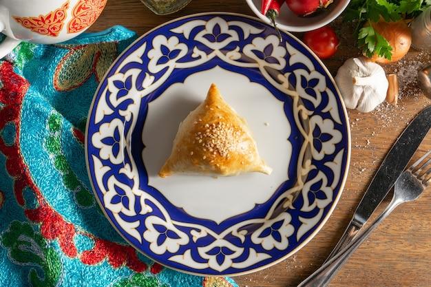 Samsa is een traditioneel oezbeeks gerecht gemaakt van deeg gevuld met fijngehakt lamsvlees met uien en kruiden op een bord met een traditioneel oezbeeks patroon