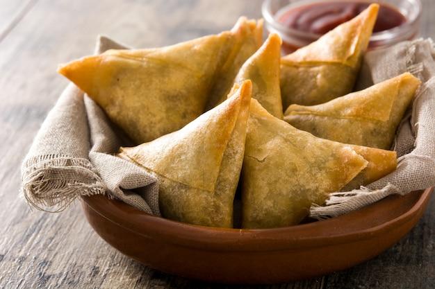 Samsa of samosas met vlees en groenten in kom op houten tafel.
