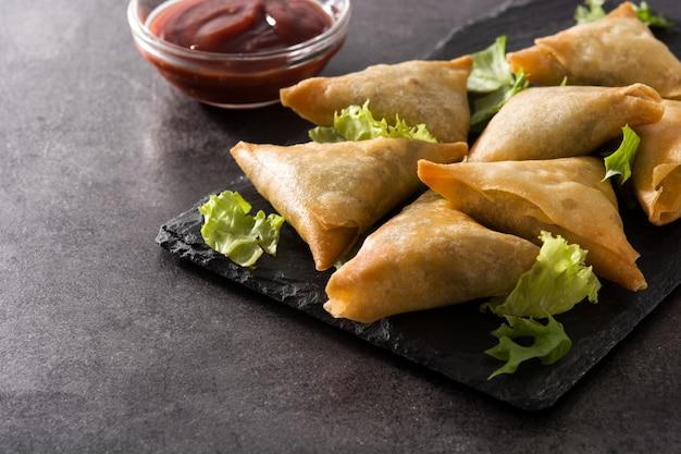 Samsa of samosas met vlees en groenten op zwart. traditioneel indiaas eten.