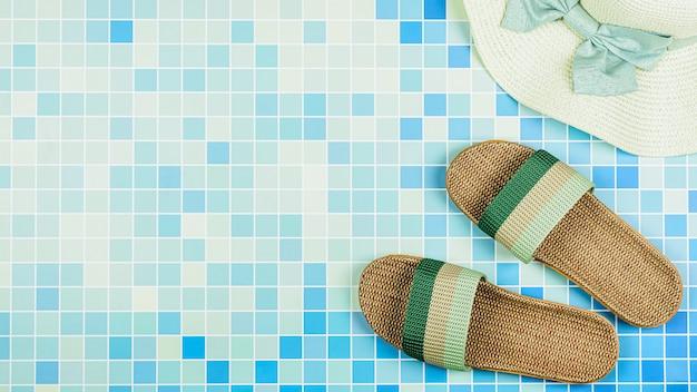 Sandalen en een strandhoed op blauwe keramische tegels bij het zwembad.